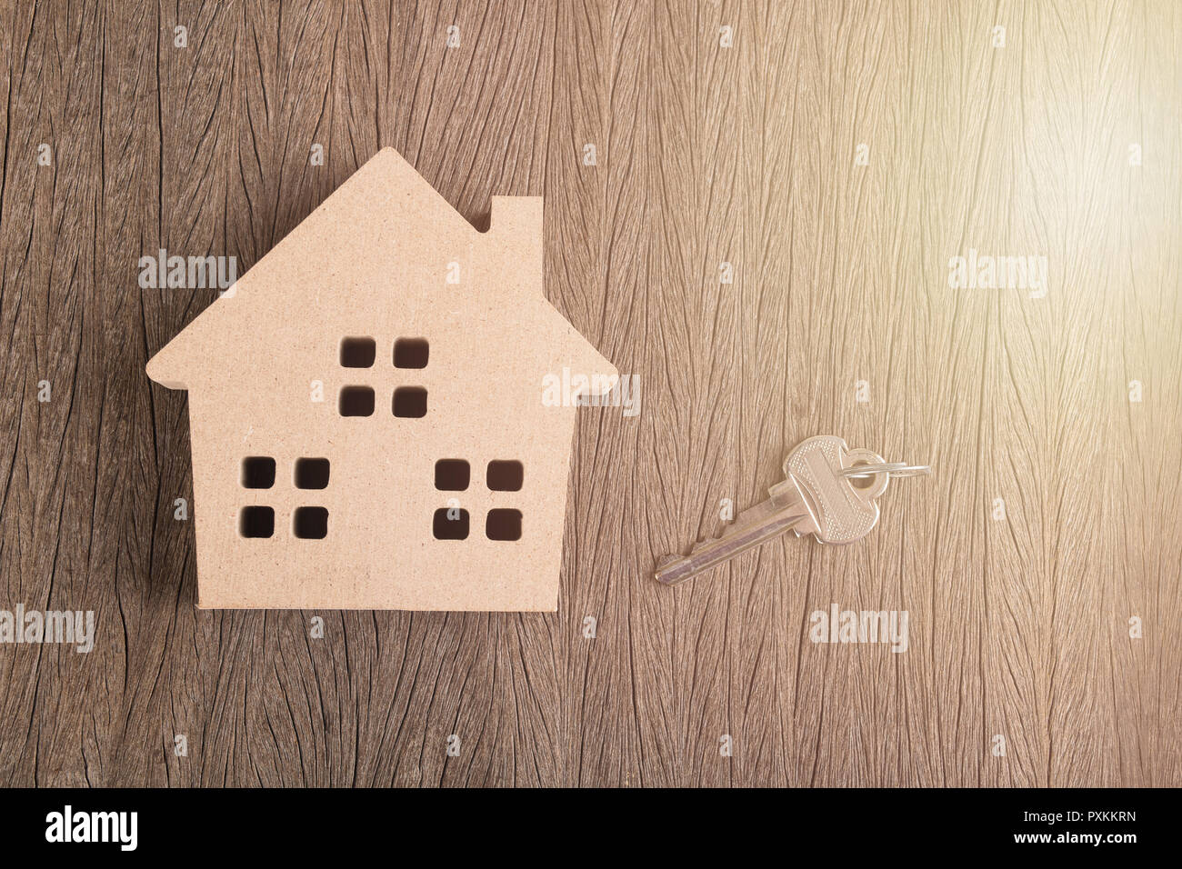 wooden house medel iwth key on wood board with morning light stock