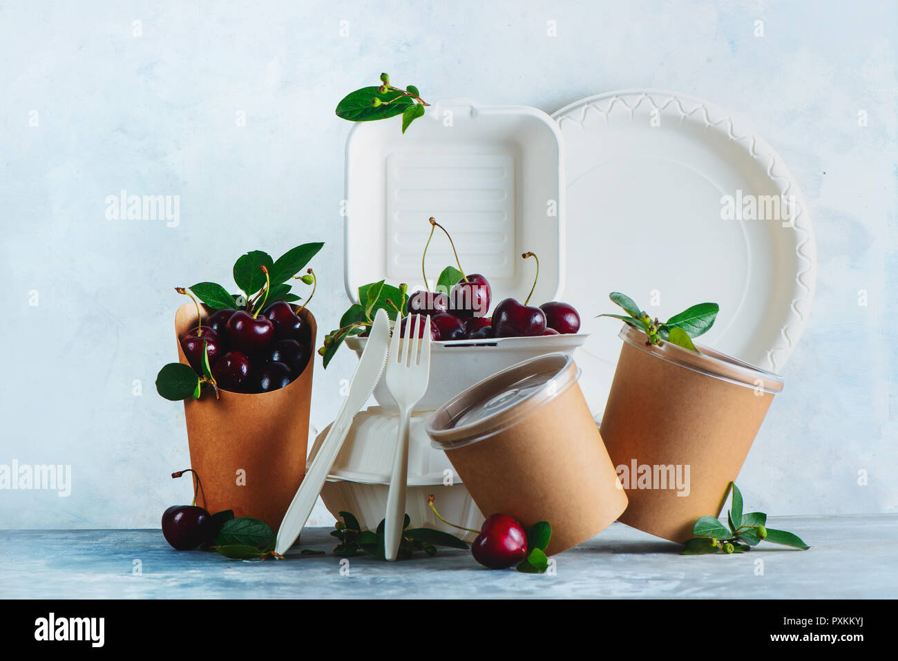 Catering disposables, cups, plates and containers with cherries. Eco-friendly food packaging on a neutral gray background with copy space. Preserving  - Stock Image