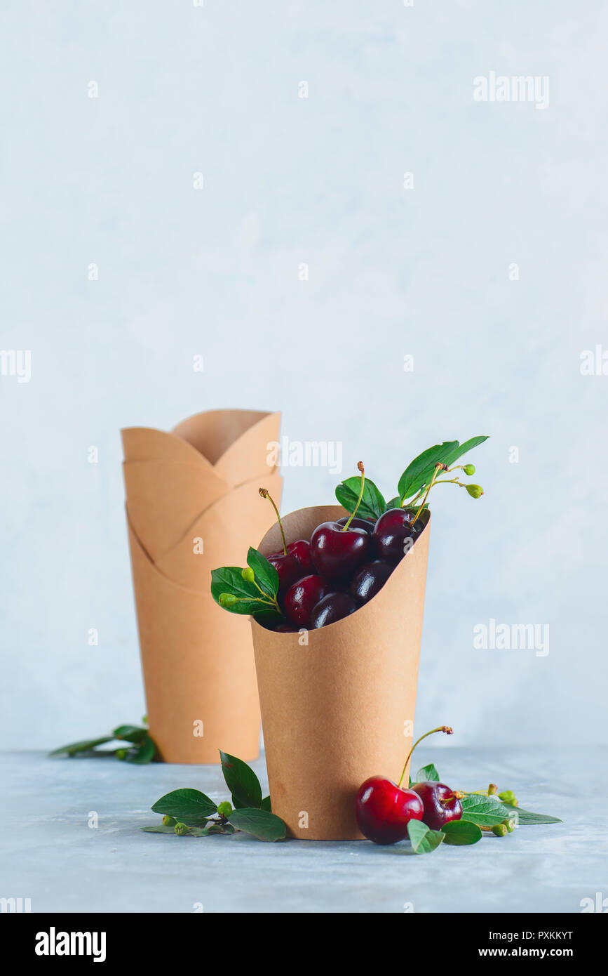 Craft paper eco-friendly food packaging with cherries. Disposable cups on a neutral gray background with copy space. Preserving nature and recycling c - Stock Image