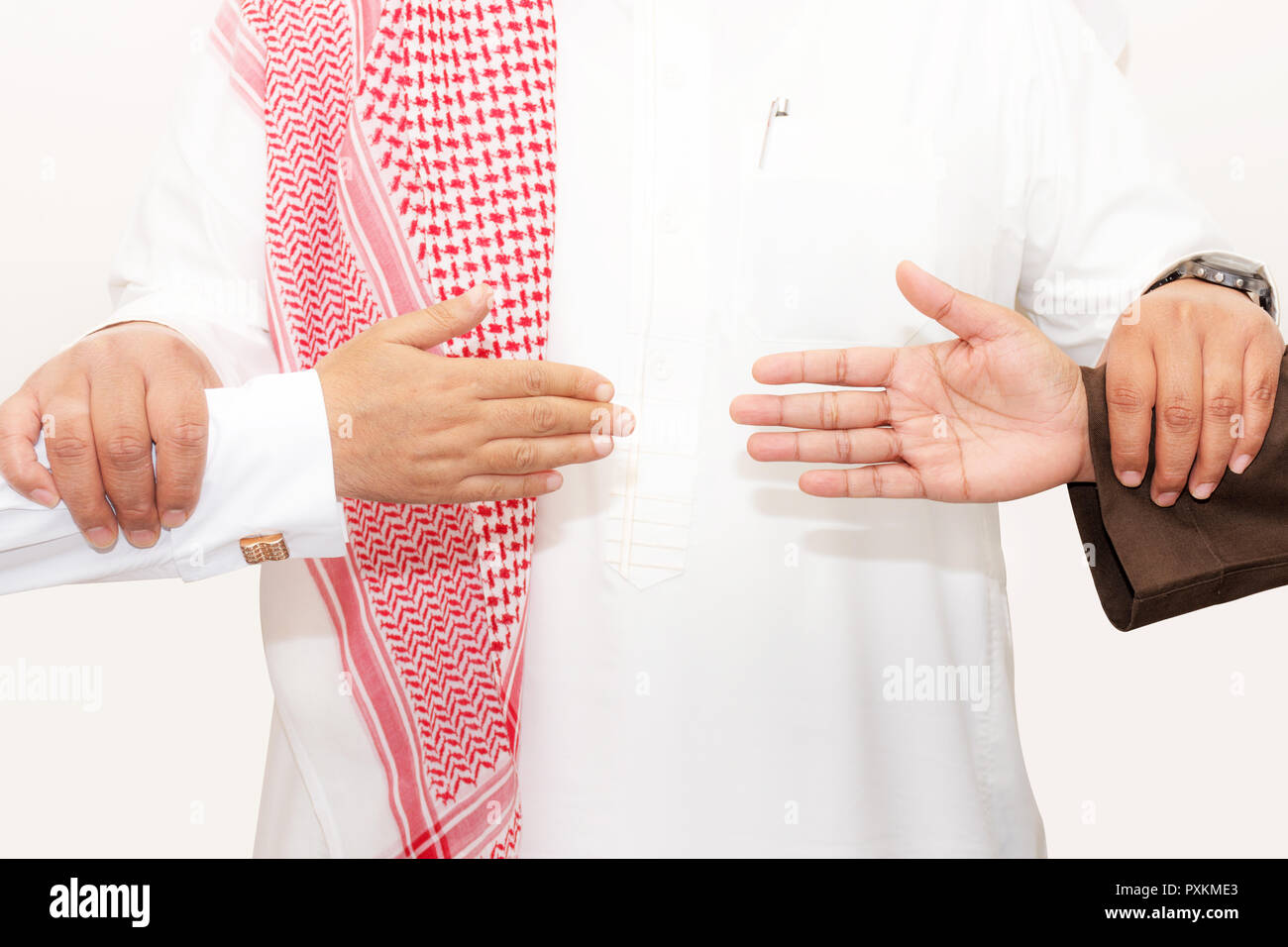 Saudi man holds two hands persons to reconciliation agreement as shake hands concept Stock Photo