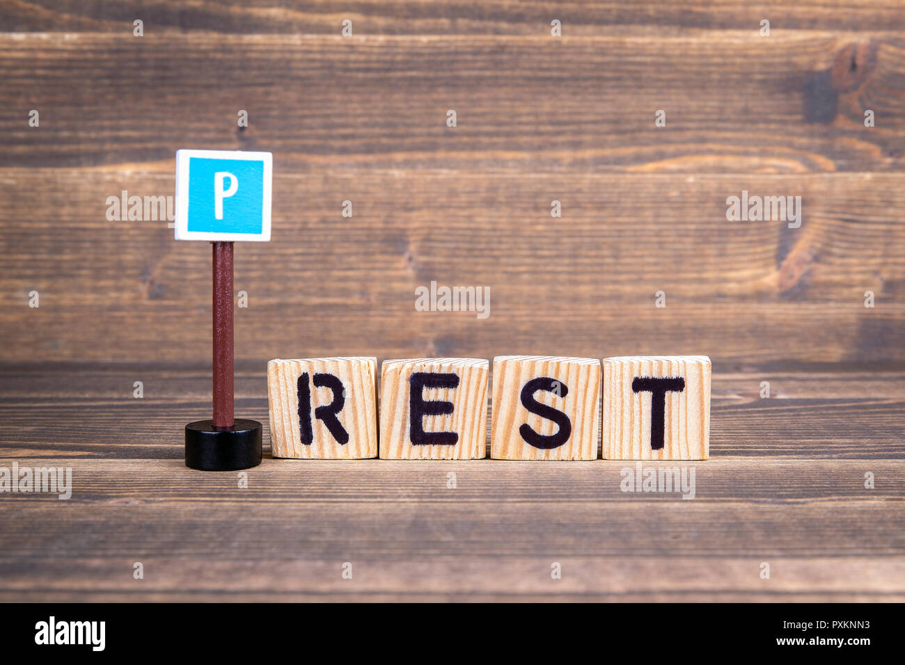 Rest name from wooden letters with road sign on wooden background - Stock Image