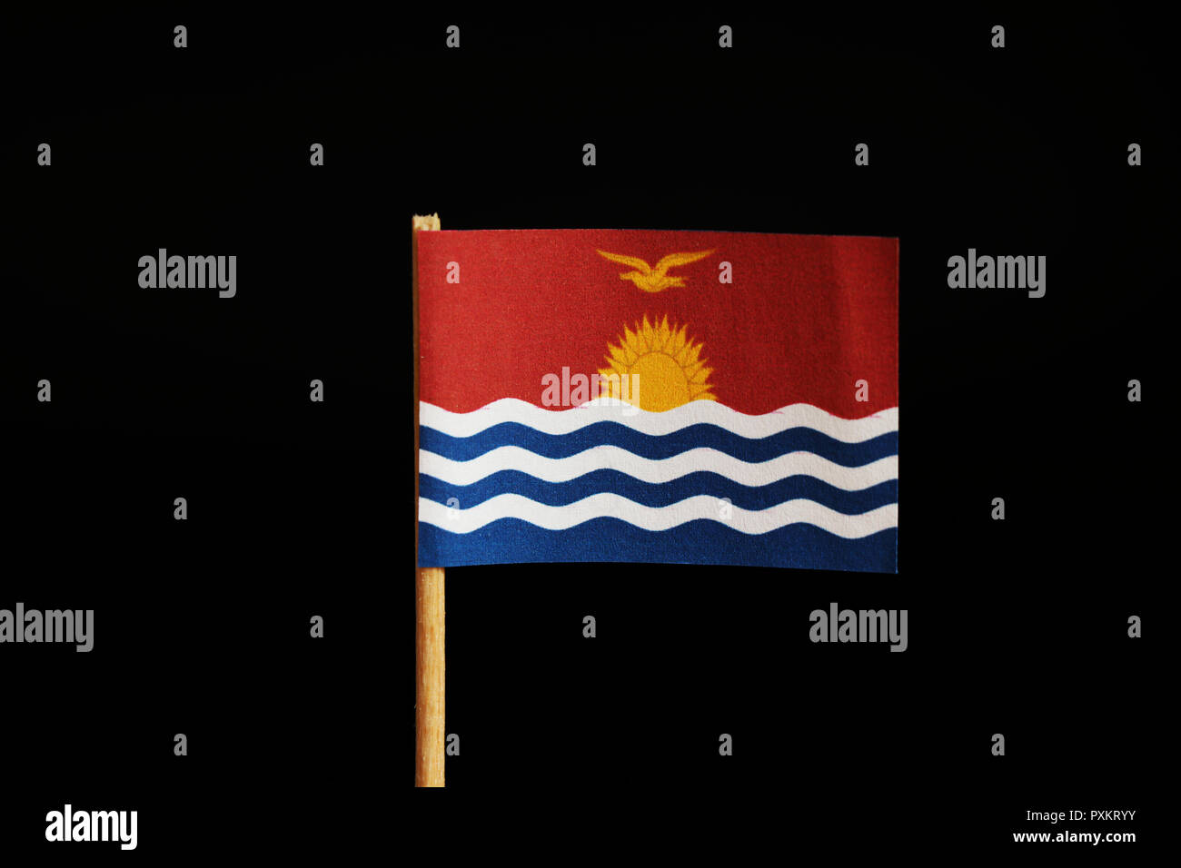 A official Flag of Kiribati on wooden stick on black background. State in the middle Oceania, pacific ocean. Sailing sun on sea. - Stock Image