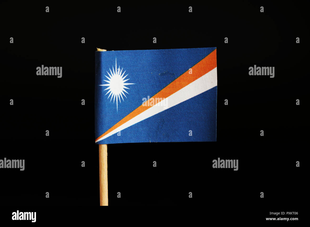 A official flag of marshall islands on wooden stick on black background. Marshall islands are located in pacific ocean and belongs to oceania. Sun on  - Stock Image