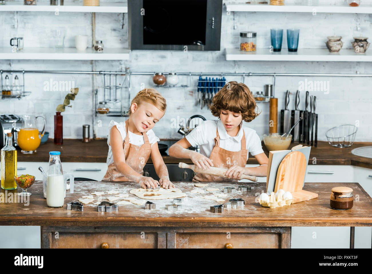 cute happy kids in aprons preparing tasty cookies together - Stock Image