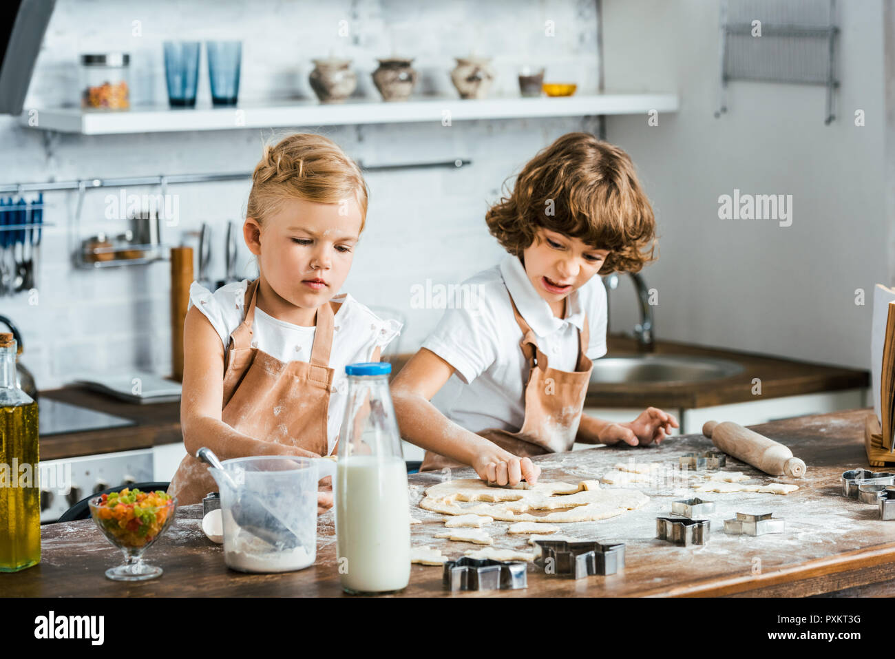 adorable children in aprons preparing dough for tasty cookies - Stock Image