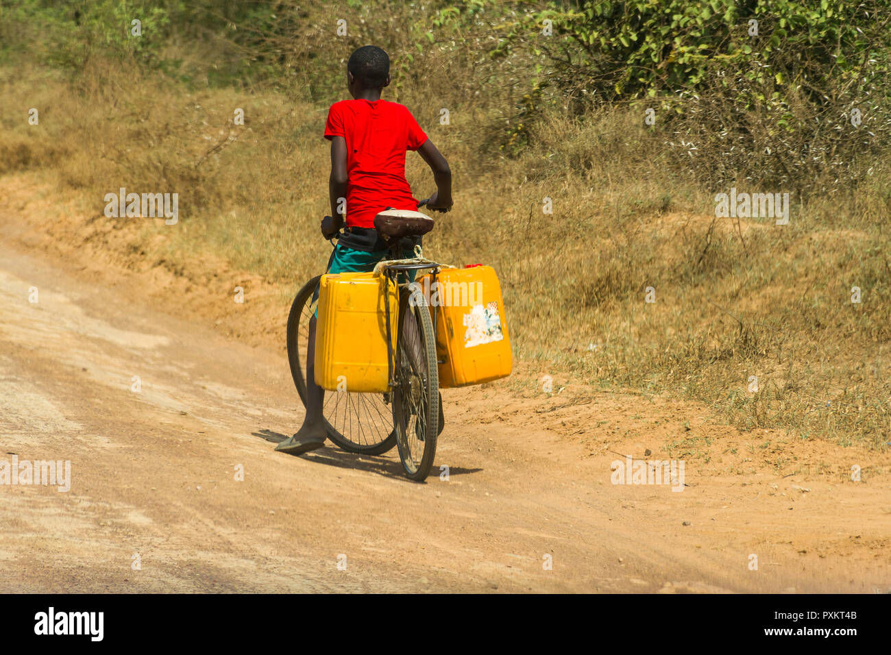 A boy cycles along a dusty road transporting water containers on the back of his bicycle, Kenya - Stock Image