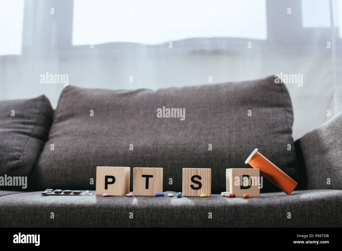 wooden cubes with posttraumatic stress disorder abbreviation signs (PTSD) lying on couch with various pills Stock Photo