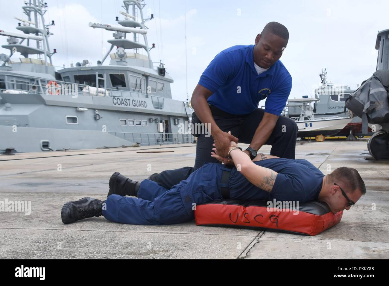 Steven Celestine, a member of the Commonwealth of Dominica Coast Guard, practices handcuffing during Exercise Tradewinds 2017 at the Barbados Coast Guard Base in Bridgetown, Barbados, June 9, 2017. Tradewinds 2017 is a joint, combined exercise conducted in conjunction with partner nations to enhance the collective abilities of defense forces and constabularies to counter transnational organized crime, and to conduct humanitarian/disaster relief operations. - Stock Image