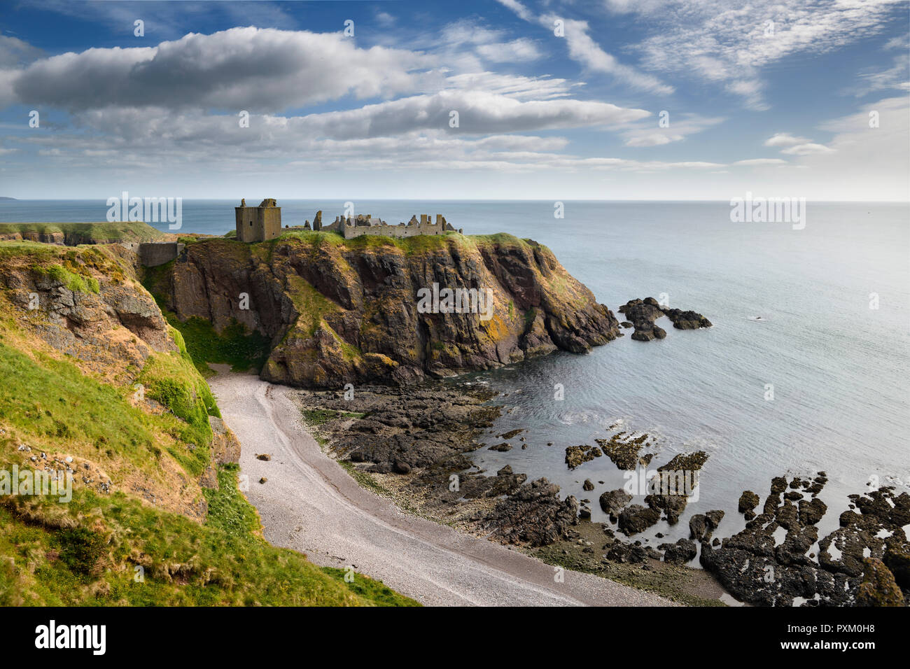 Pebble beach at Old Hall Bay North Sea with Donnottar Castle Medieval clifftop fortress ruins near Stonehaven Scotland UK - Stock Image