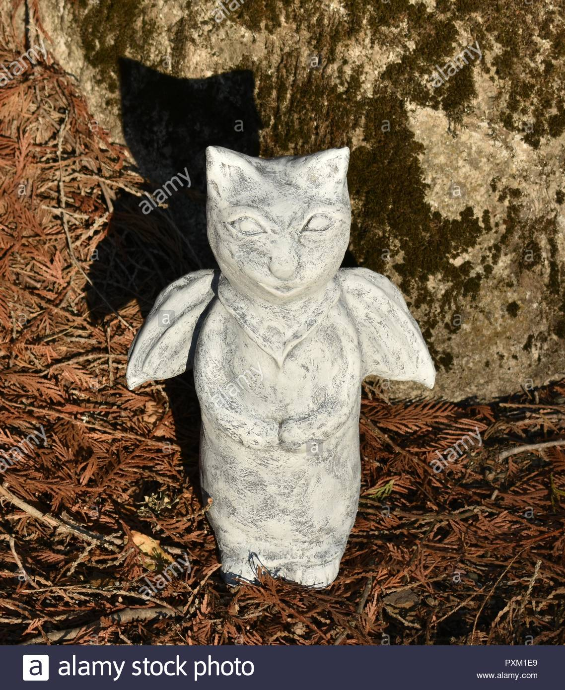 Sunlight on bat cat sculpture casting shadow on moss covered boulder rock - Stock Image