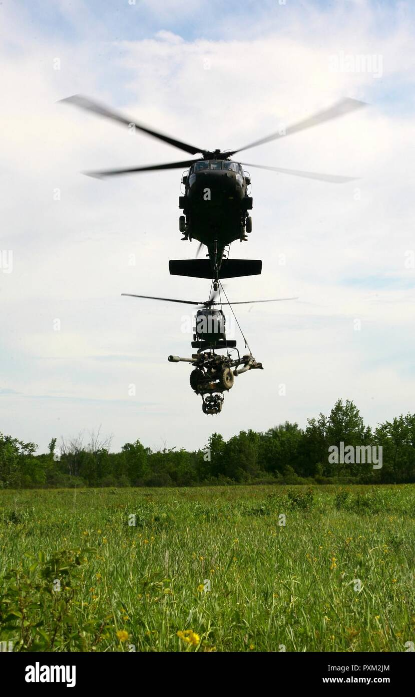New York Army National Guard  UH-60 Blackhawk helicopters from the 42nd  Combat Aviation Brigade transports two M119A2 Howitzers to a landing zone during an air assault artillery raid at Fort Drum on June 9, 2017. The raid, which was conducted in conjunction with Soldiers from Alpha Troop, 1st Battalion, 258th Field Artillery Regiment, 27th Infantry Brigade Combat Team, involved transporting the 4 howitzers to a landing zone then utilizing them to engage a simulated enemy target. Stock Photo