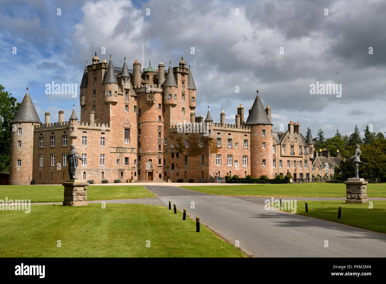 Front lawn of Glamis Castle childhood home of Queen Mother with statues of King James I and Charles I with sun and clouds Scotland UK - Stock Image