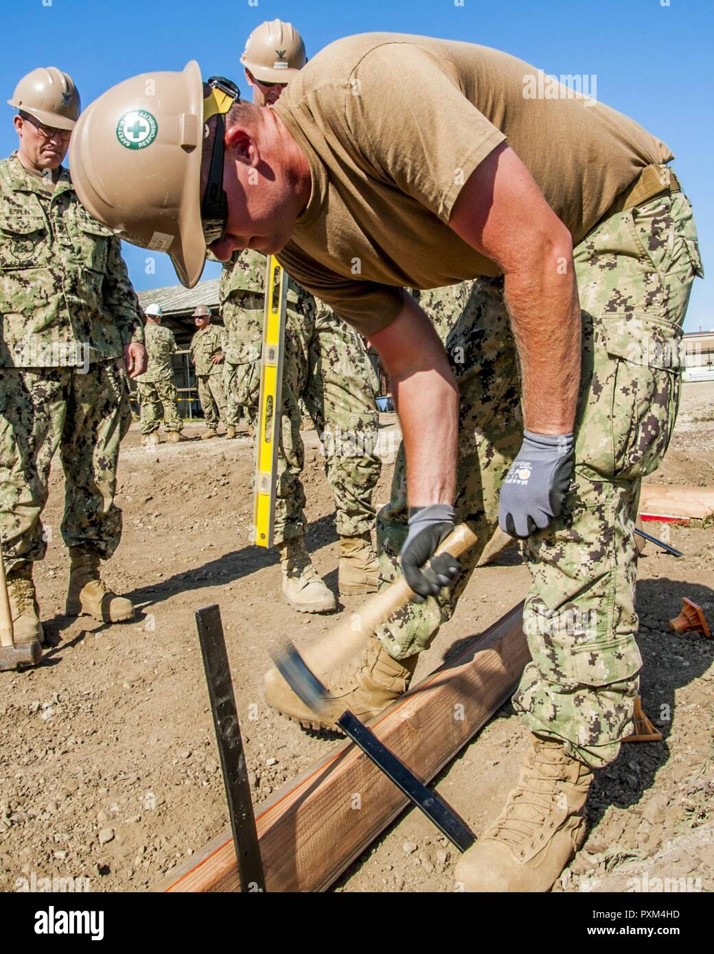 PORT HUENEME, Ca. (JUNE 9, 2017) – Petty Officer 1st Class Alan Eslinger with Naval Mobile Construction Battalion 18 (NMCB 18) hammers in a support bar for a concrete form as part of a driveway extension project. NMCB 18 is building the concrete driveway extension on Naval Base Ventura County. The base will utilize the driveway for movement and transportation operations. - Stock Image