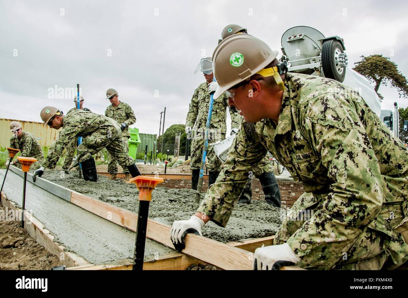 PORT HUENEME, Ca. (JUNE 10, 2017) – Sailors attached to Naval Mobile Construction Battalion 18 (NMCB 18), use a screed to level fresh poured concrete during a driveway extension project. NMCB 18 is building the concrete driveway extension on Naval Base Ventura County. The base will utilize the driveway for movement and transportation operations. U.S. Navy Photo by Mass Communication Specialist 2nd Class Ian Carver/RELEASED). - Stock Image