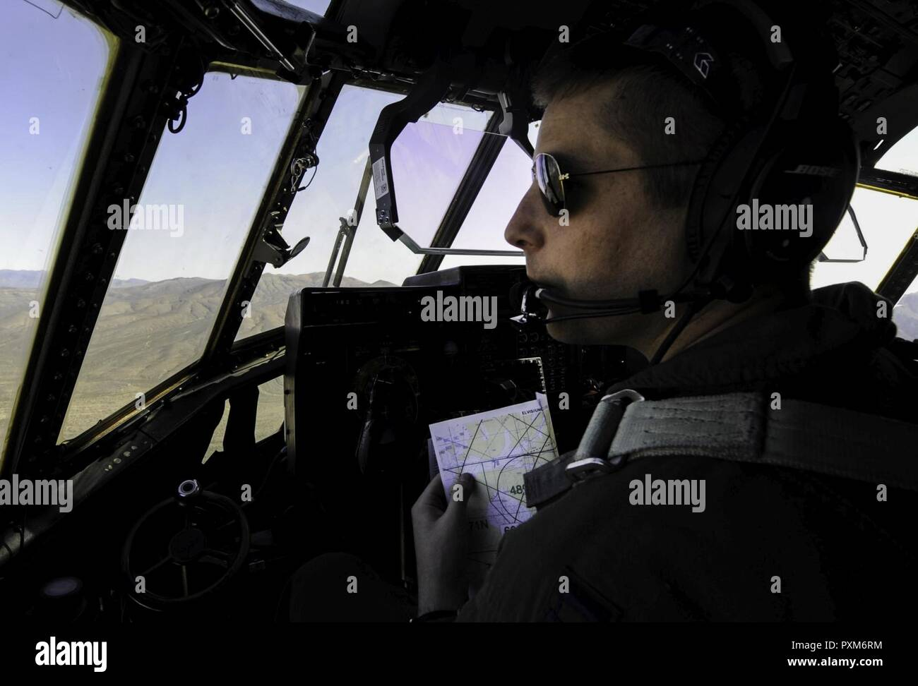 A pilot verifies coordinates on a map during a Weapons School Integration mission over the Nevada Test and Training Range, Nev., June 2, 2017. The students who take the Weapons School course demonstrate their ability to manage a battle and effectively integrate multiple weapons systems. - Stock Image