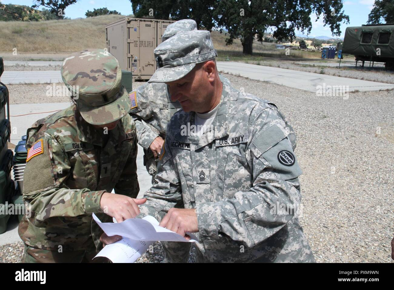 (Left) U.S. Army 1st Lt. Majken Geiman and (Right) Sgt. 1st Class Hugh Becker of the 698th Quartermaster Company discuss troop counts and plans to expedite the chow line at Tactical Assembly Area Ward on June 11, 2017 on Fort Hunter Liggett, Calif. More than 3000 U.S. Army Reserve Soldiers are participating in the 91st Training Division's Warrior Exercise 91-17-03 at Fort Hunter Liggett, California; the Warrior Exercise is a large scale collective training platform to generate capable, lethal and combat ready forces. - Stock Image