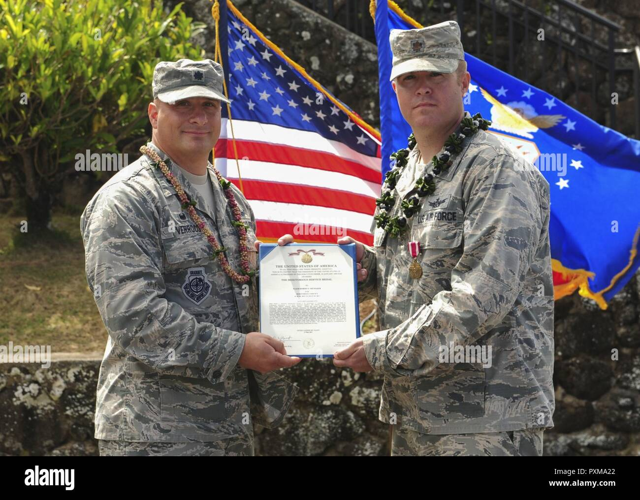 Lt. Col. Phillip Verroco, 21st Space Operations Squadron commander, presents Maj. Robert F. Shumaker, Detachment 3 outgoing commander, with the Meritorious Service Medal during the Detachment 3 Change of Command Ceremony, Kaena Point, Hawaii, June 9, 2017.  Detachment 3 is a component of the 21st Space Operations Squadron, 50th Network Operations Group, 50th Space Wing, and is located on the western tip of Oahu.  It is the oldest and one of seven worldwide remote tracking stations in the Air Force Satellite Control Network. - Stock Image