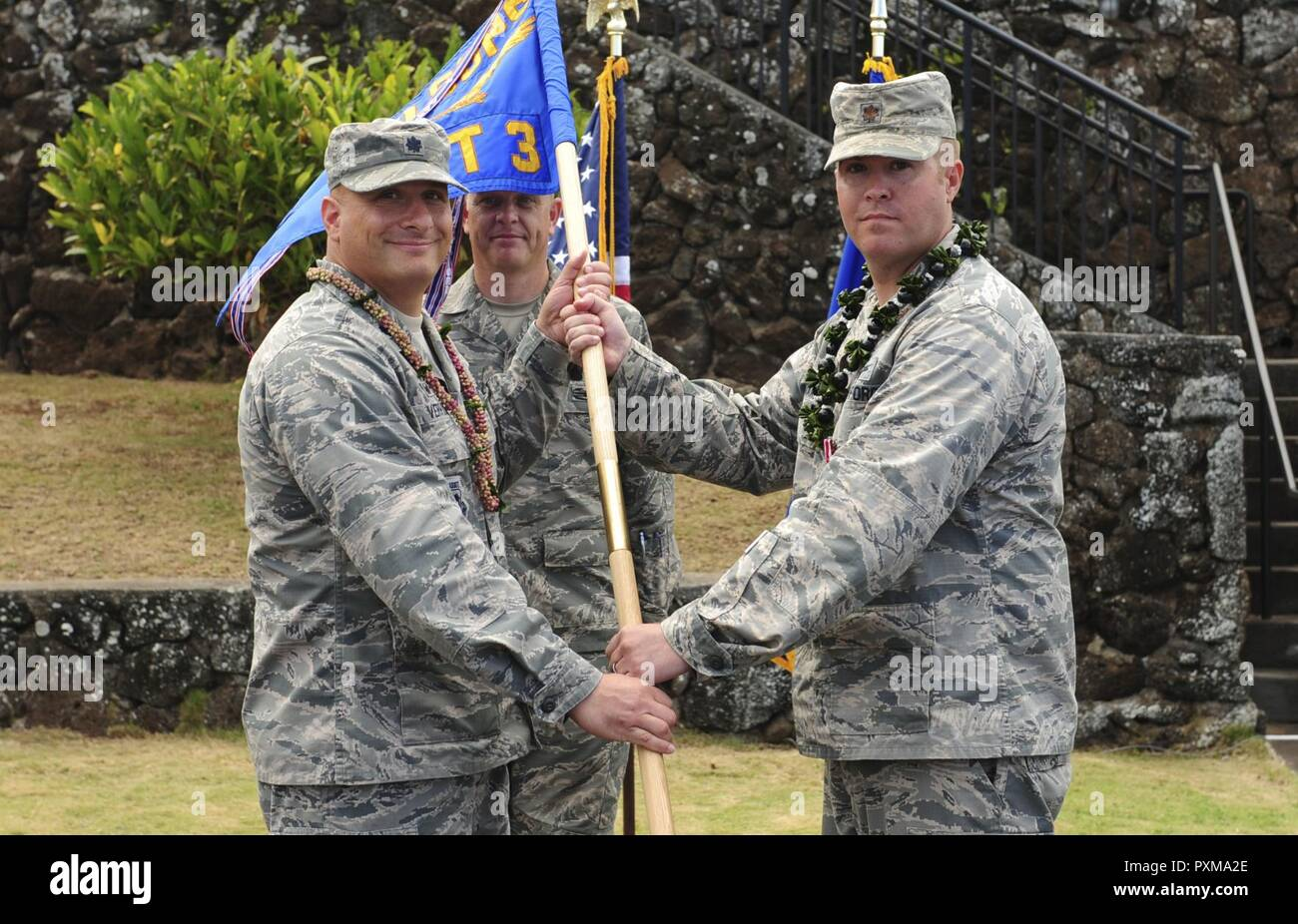 Lt. Col. Phillip Verroco, 21st Space Operations Squadron commander, takes the detachment flag from Maj. Robert F. Shumaker, Detachment 3 outgoing commander, during the Detachment 3 Change of Command Ceremony, Kaena Point, Hawaii, June 9, 2017.  Detachment 3 is a component of the 21st Space Operations Squadron, 50th Network Operations Group, 50th Space Wing, and is located on the western tip of Oahu.  It is the oldest and one of seven worldwide remote tracking stations in the Air Force Satellite Control Network. - Stock Image