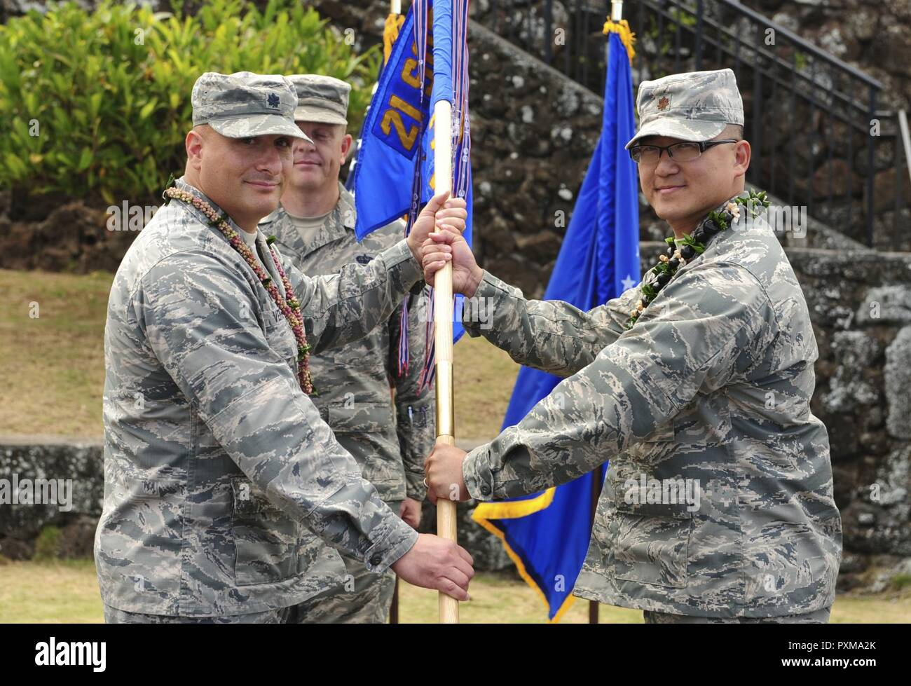 Lt. Col. Phillip Verroco, 21st Space Operations Squadron commander, gives the detachment flag to Maj. Edmond Chan, Detachment 3 incoming commander, during the Detachment 3 Change of Command Ceremony, Kaena Point, Hawaii, June 9, 2017.  Detachment 3 is a component of the 21st Space Operations Squadron, 50th Network Operations Group, 50th Space Wing, and is located on the western tip of Oahu.  It is the oldest and one of seven worldwide remote tracking stations in the Air Force Satellite Control Network. - Stock Image
