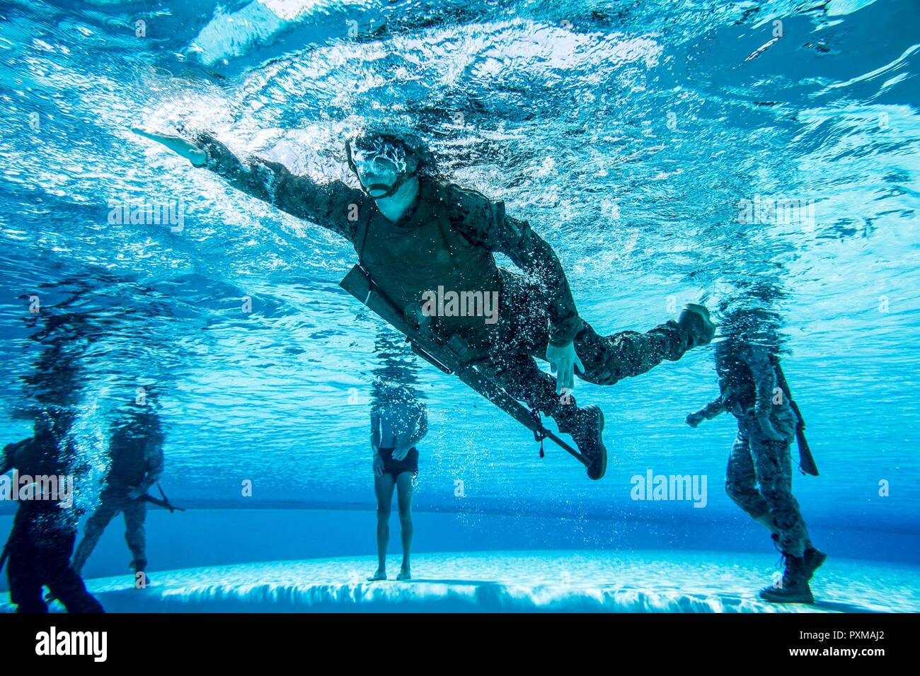 A U.S. Marine with 1st Marine Logistics group participates in the water survival advanced course on Camp Pendleton, Calif., June 14, 2017. The purpose of the water survival course is to strengthen the individual Marine's self-preservation and rescue skills in water. 1st MLG is home to multiple military occupations that work together to provide support to each element of the 1st Marine Expeditionary Force through logistics beyond the capabilities of the supported units. Stock Photo