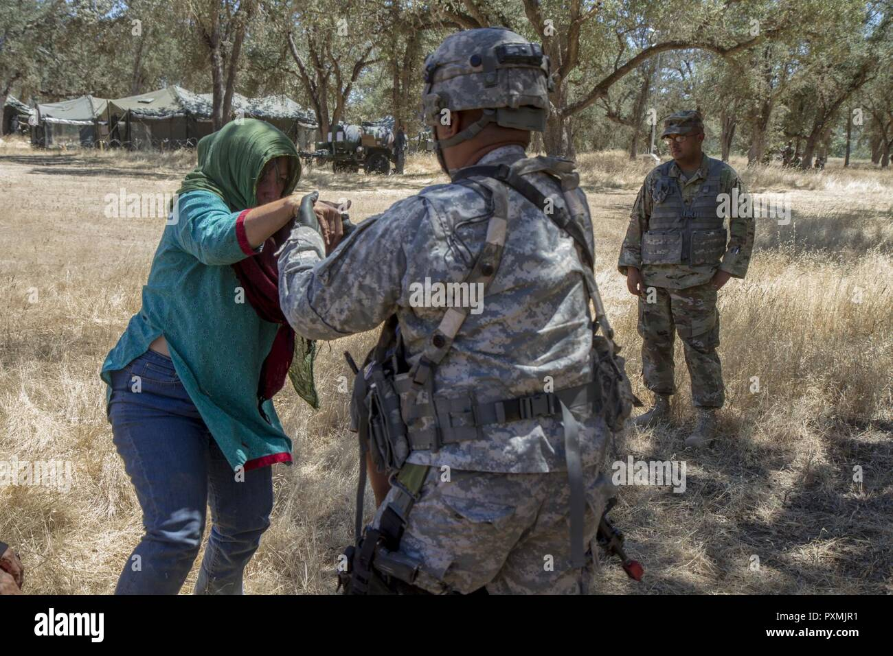 U.S. Army Staff Sgt. Eric Manalansan, 491st Military Police Company out of Riverside, Calif., helps Ms. Rebecca Riel, computer illustrator from Lockwood, Calif., to her feet, while she is role playing as a local villager in their training exercise during the 91st Training Division's Warrior Exercise (WAREX) 91-17-03 on Fort Hunter Liggett, Calif. on June 15, 2017. Their training scenario involved providing medical aid for local villagers entering their Tactical Assembly Area, this is to prepare them for similar encounters they may face while deployed overseas. - Stock Image