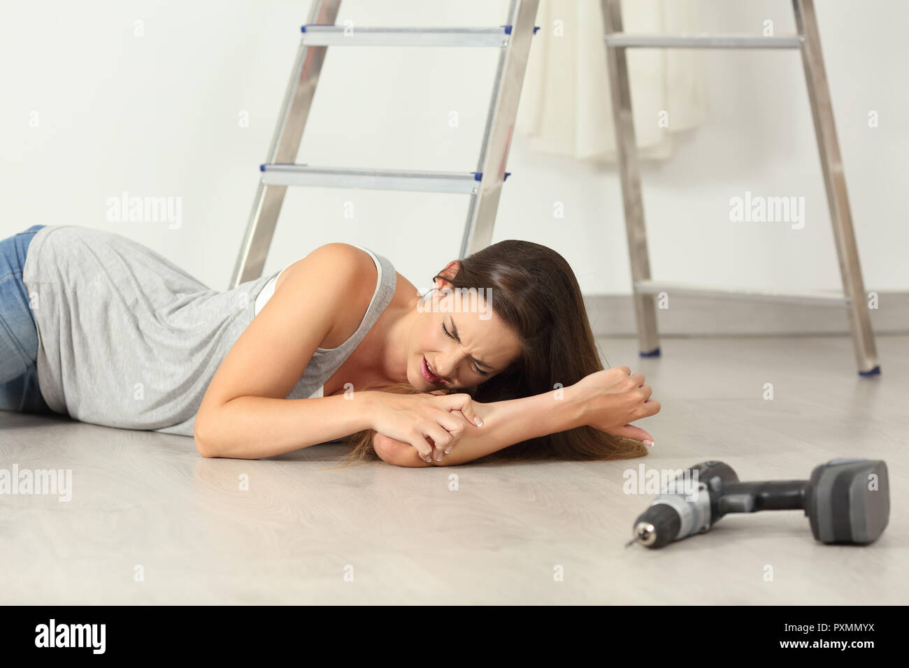 Woman complaining after domestic accident on the floor at home - Stock Image