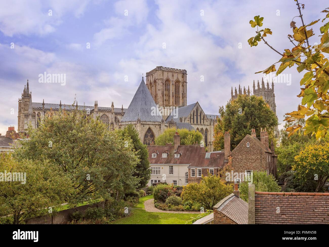 York Minster rises from amongst some buildings with a garden in front. Autumnal trees abound. Stock Photo
