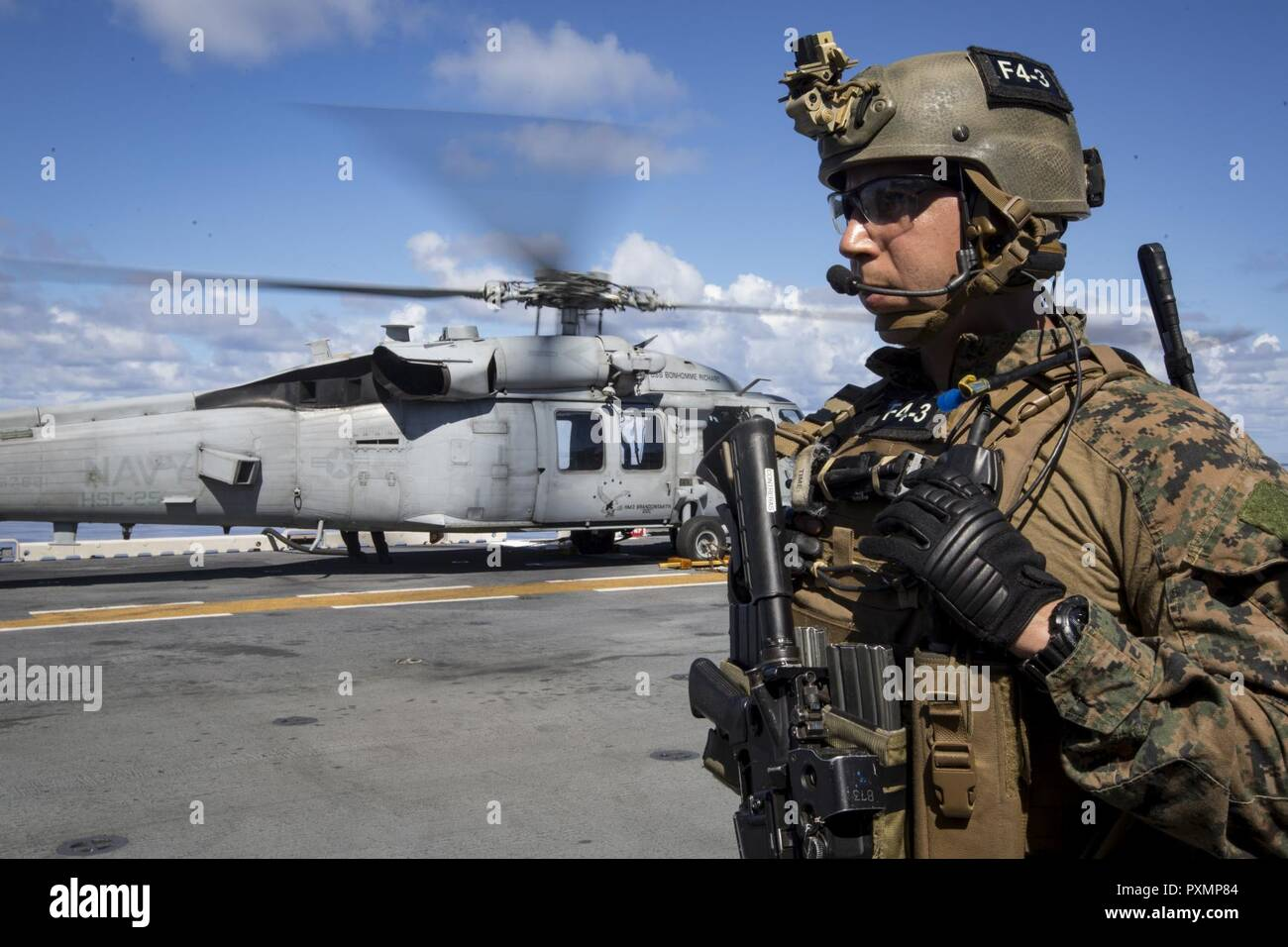 Staff Sgt. Abel Contreras, communications chief with the 31st Marine Expeditionary Unit's Force Reconnaissance Platoon (FRP), waits to board an MH-60S Sea Hawk helicopter aboard the USS Bonhomme Richard (LHD 6) before launching for vessel Visit, Board, Search and Seizure (VBSS) training, June 15, 2017.  During VBSS, Marines with FRP board vessels via rotary-wing aircraft or surface boats in response to a terrorist threat, to interdict pirates and smugglers or to disrupt criminal activity.  The 31st MEU partners with the Navy's Amphibious Squadron 11 to form the amphibious component of the Bonh Stock Photo