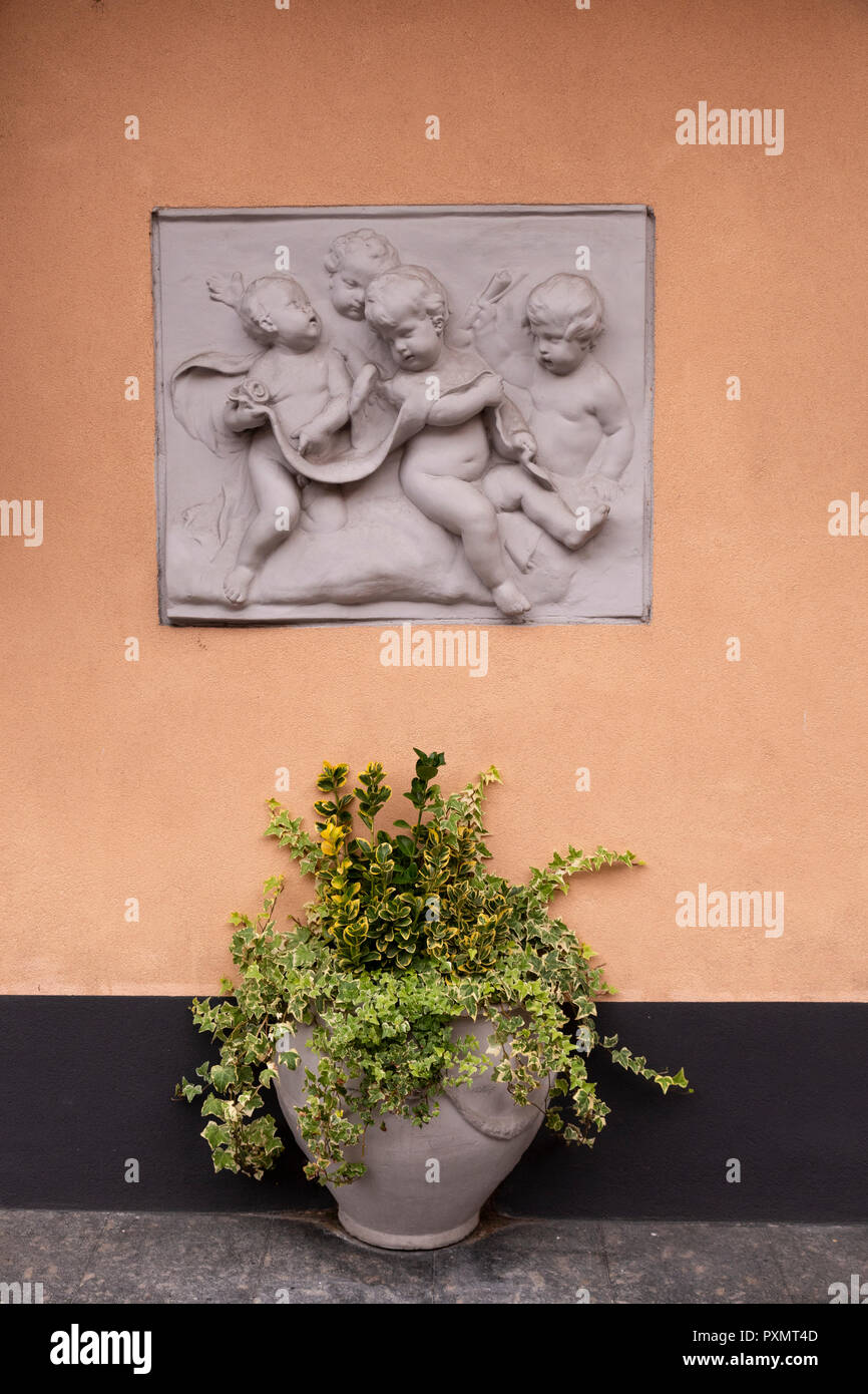 Carving of cherubs on a wall at Bellagio, Lake Como, Italy with a plant in a pot Stock Photo