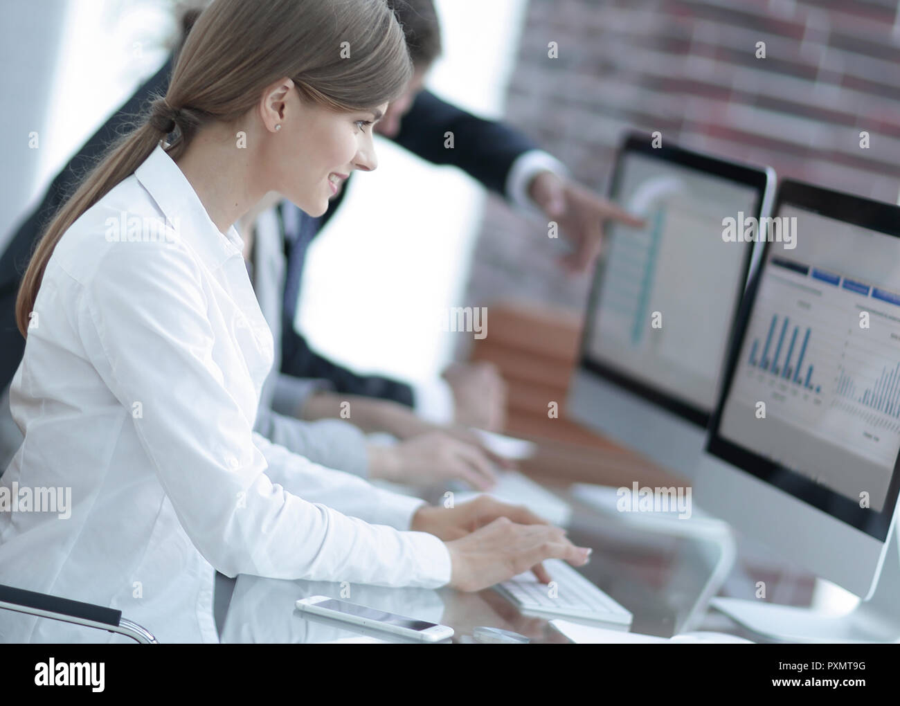 business team working on computers with financial data. - Stock Image
