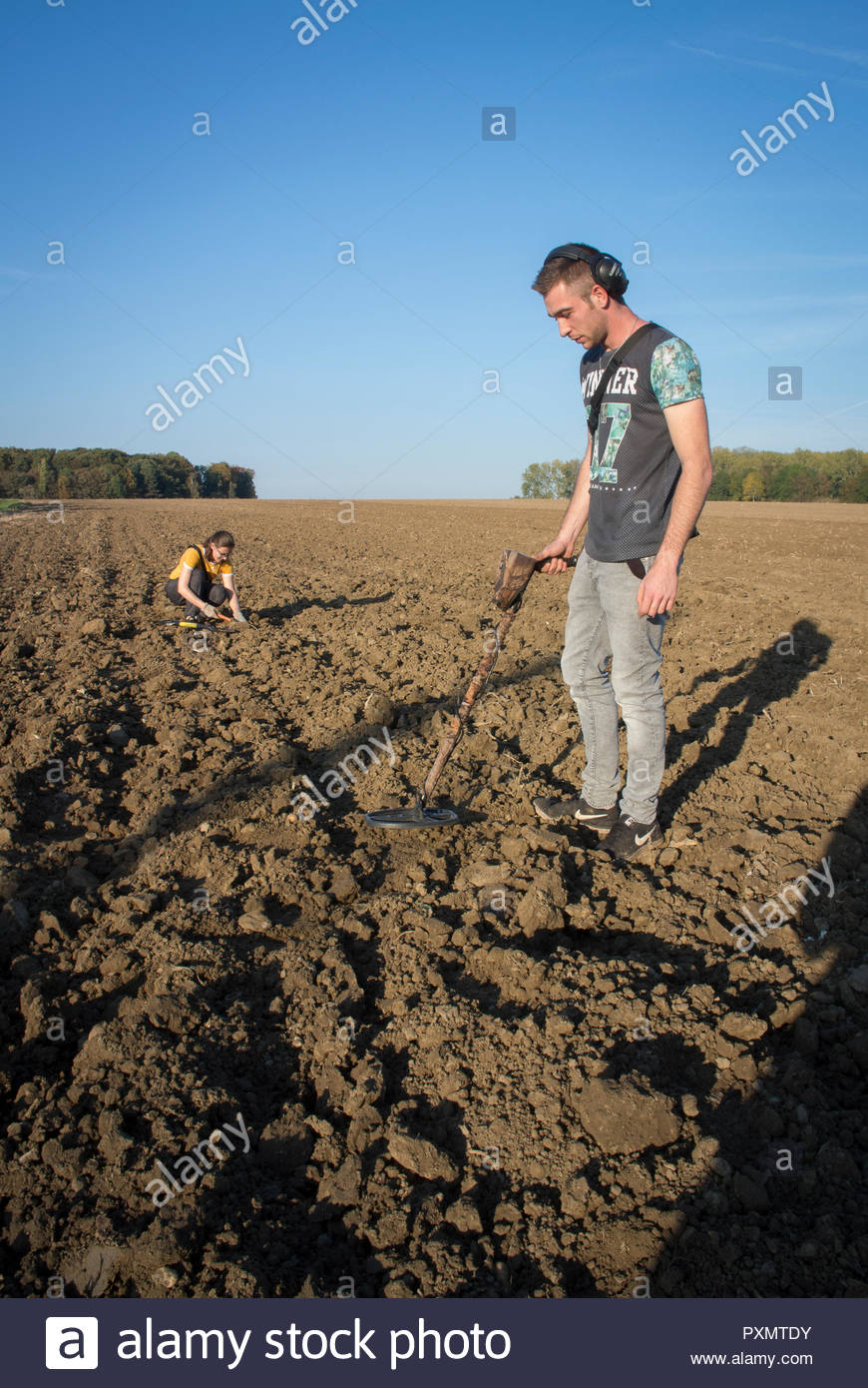 Mine detector enthusiasts Jeffrey Antonissen with his girl friend Tonje Brack scouring the ploughed fields outside Ypres, Belgium - Stock Image