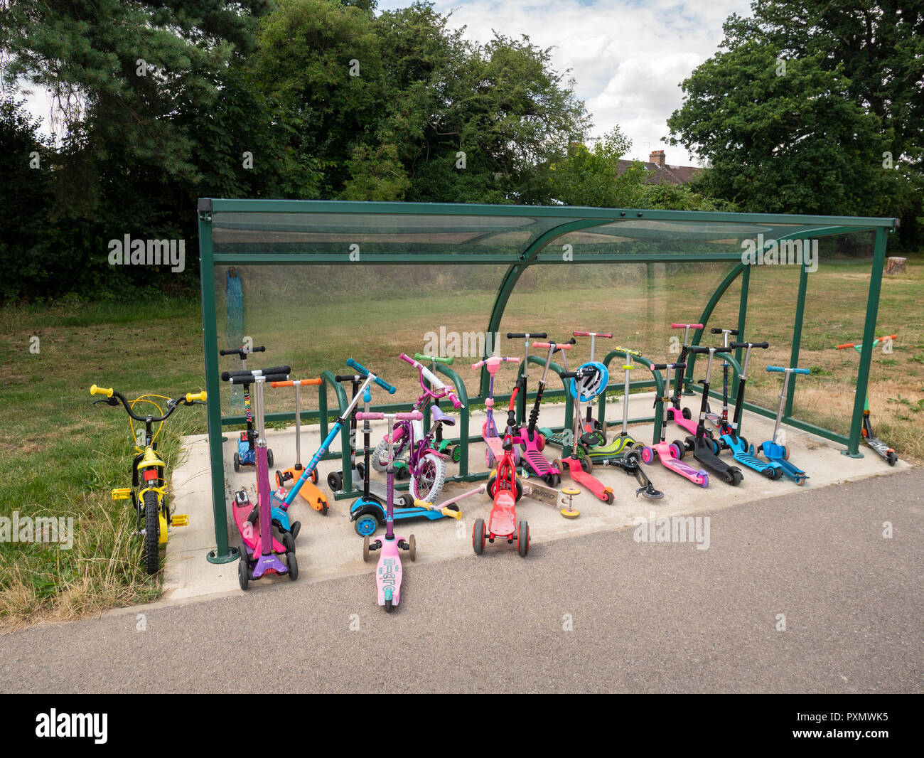 Children's scooters parked up at Worcesters Primary School, Enfield, UK, London - Stock Image