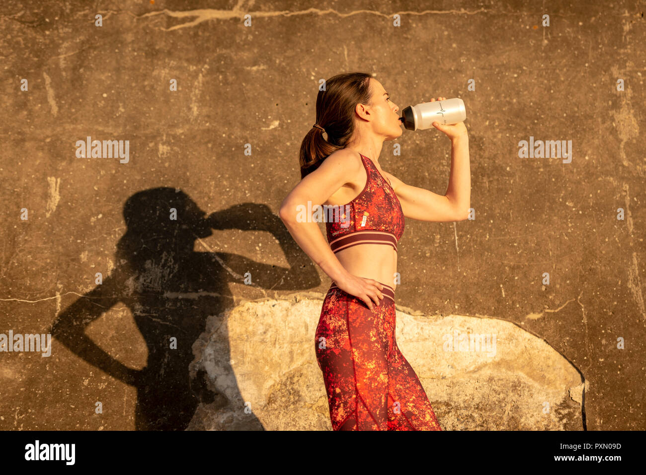 sportswoman drinking water from a bottle in the sun - Stock Image