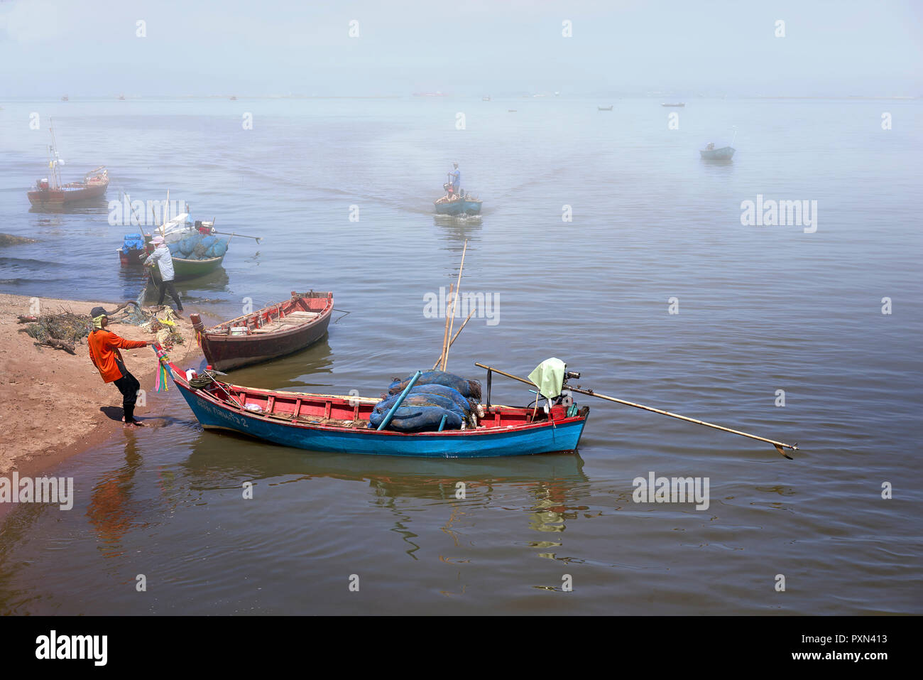 Fog descending at a fishing port with boats heading home to moor. Thailand Southeast Asia - Stock Image