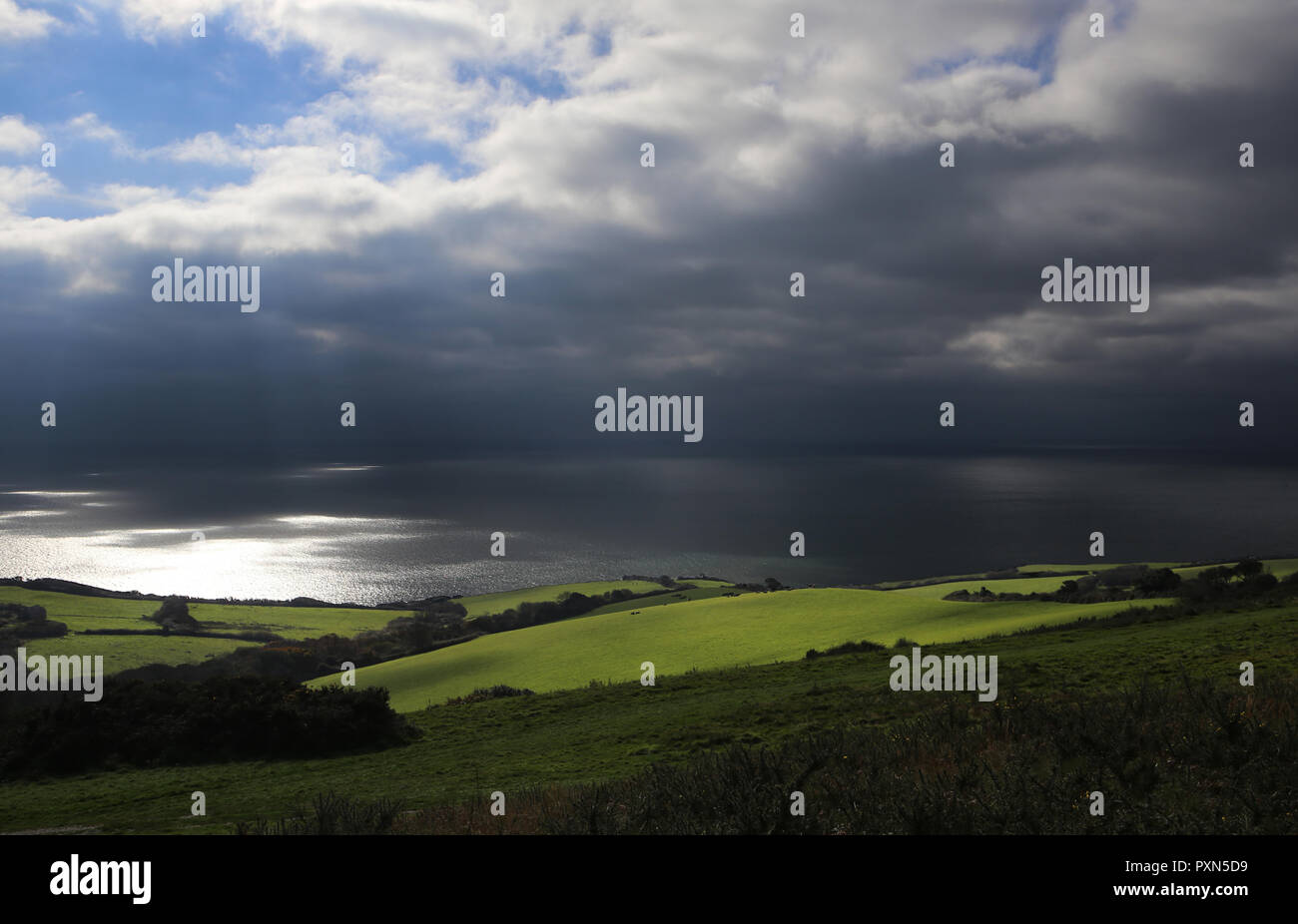 Sun shining through clouds onto green field on Dorset coast - Stock Image