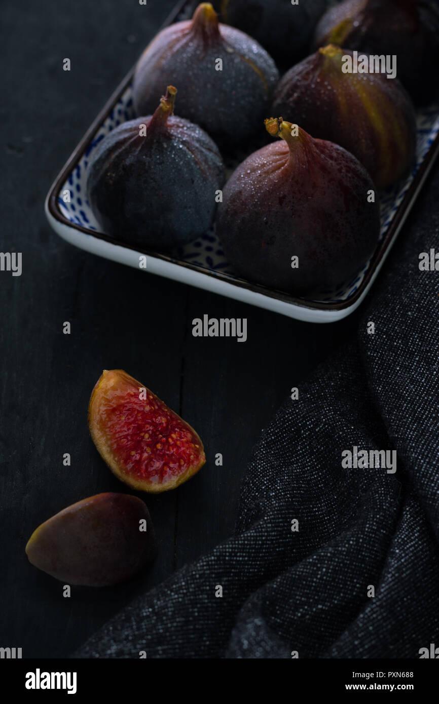 Frische Feigen in einer Porzellanschale auf dunklen Holzuntergrund mit dunklem Hintergrund - Stock Image