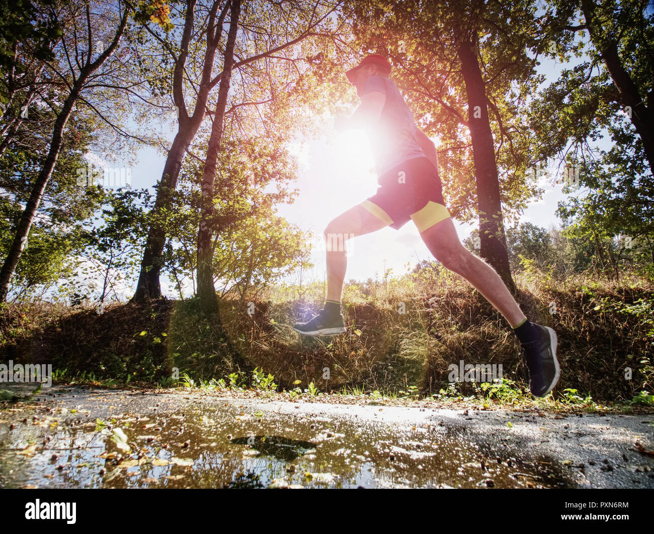 Jogging tall sports man in trees shadows with sun light behind him while wearing black yellow shorts and blue jogging attire - Stock Image