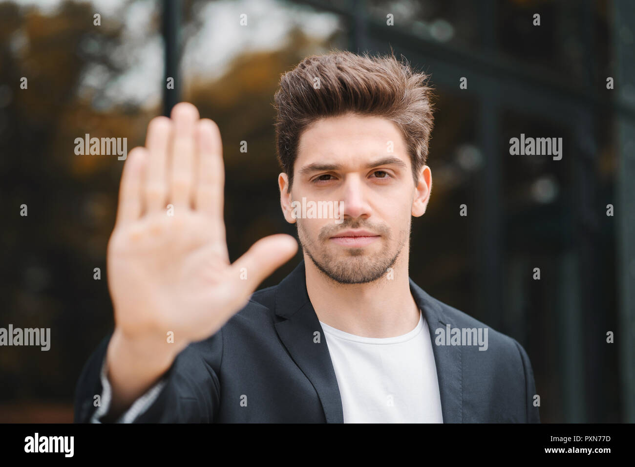Portrait of young businessman disapproval gesture with hand: denial sign, no sign, negative gesture closes the camera with hand, professional male manager wearing suit jacket. - Stock Image