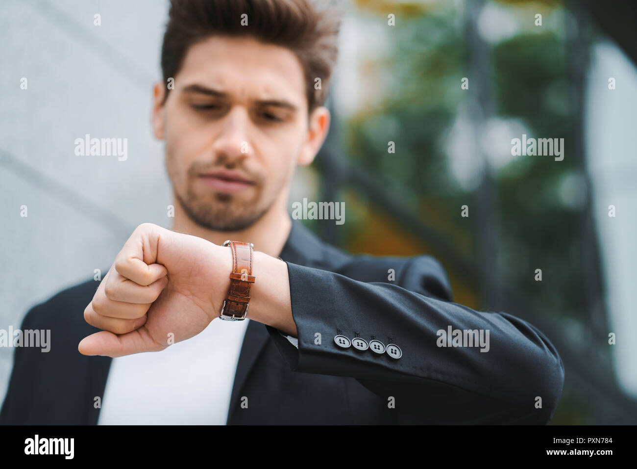 Handsome businessman or student looks at watch. Young man in hurry late for work. Male model on office building background - Stock Image