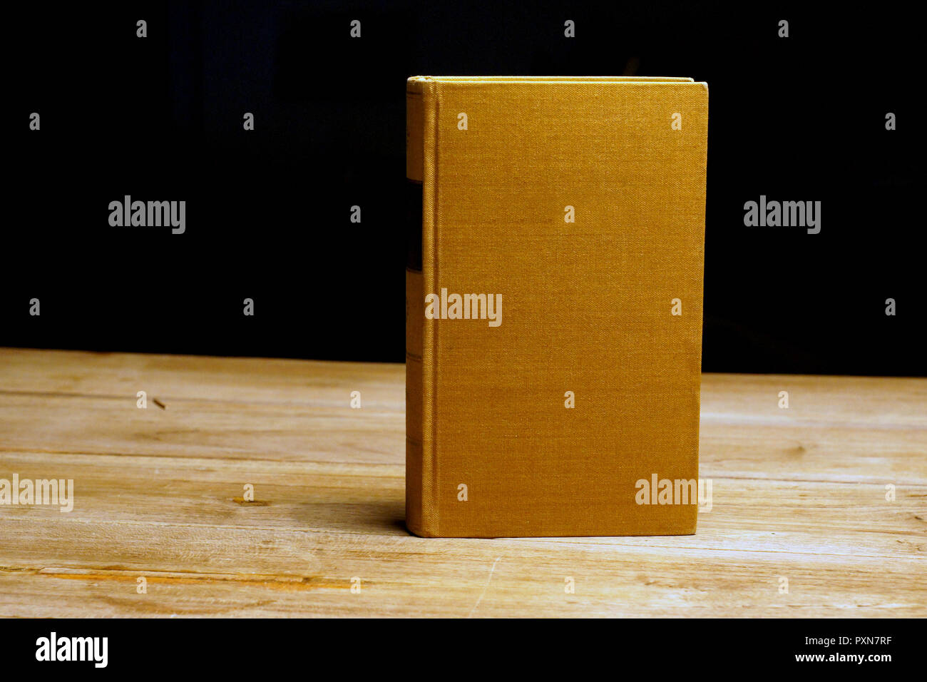 brown old hard covered book at wooden table - Stock Image
