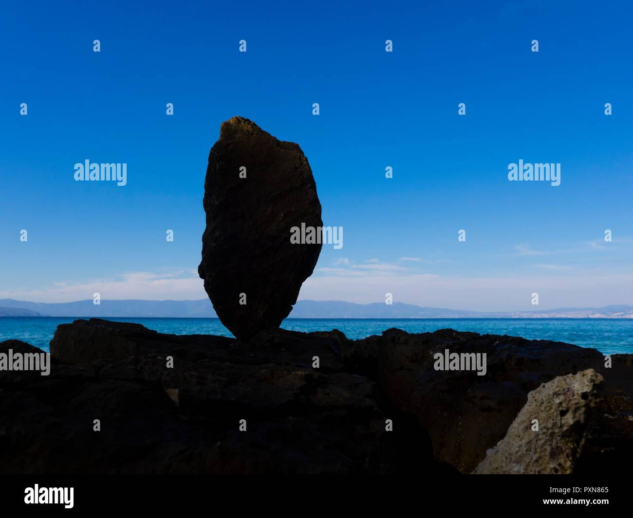 Single rock tip-toeing on seaside against clear Blue sky and calm sea horizon - Stock Image
