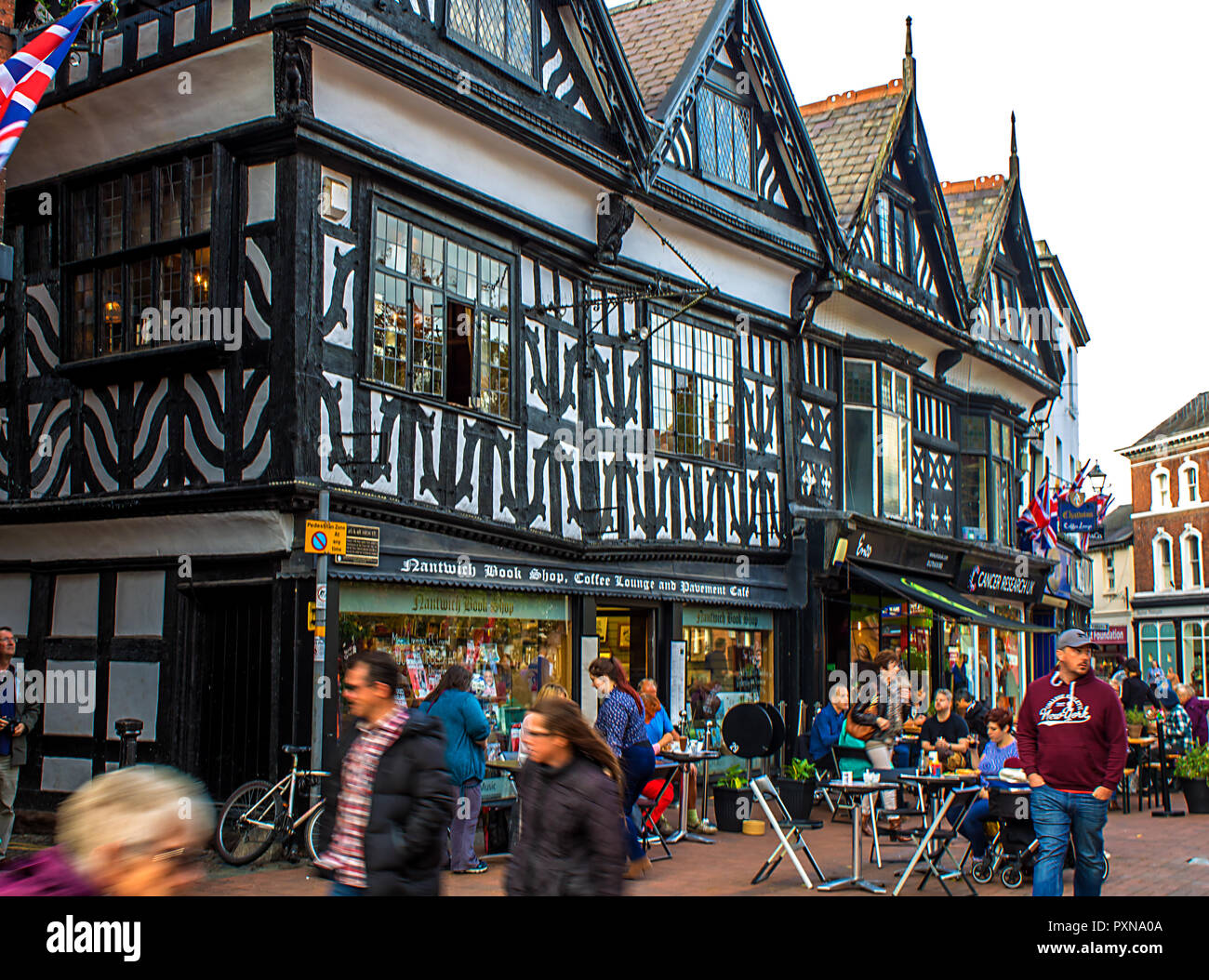 Bustling crowds outside the tudor shops in Nantwich High Street, Cheshire, UK - Stock Image