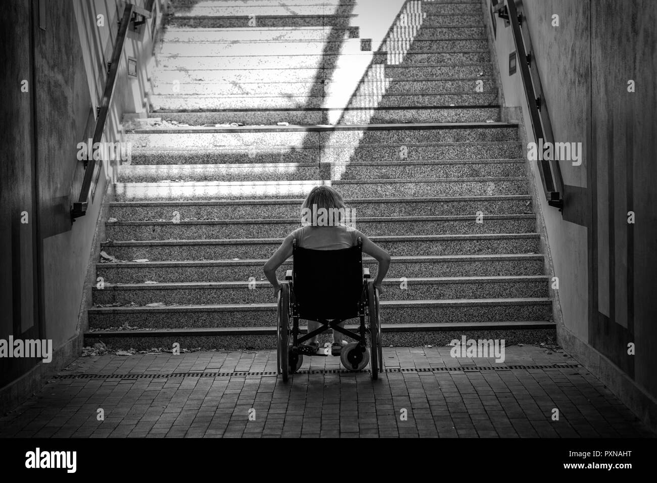 woman on wheelchair standing before stairs looking up for help - Stock Image