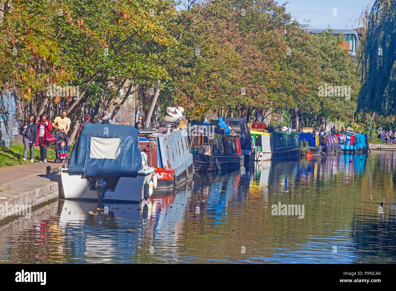 Houseboats on a stretch of Regent's Canal near Camden Lock, with walkers on the towpath. - Stock Image
