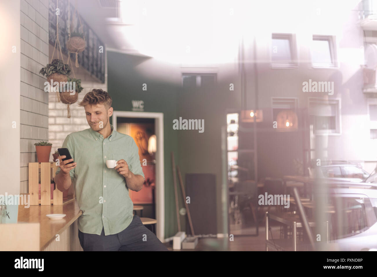 Young business owner drinking coffee, checking smartphone - Stock Image