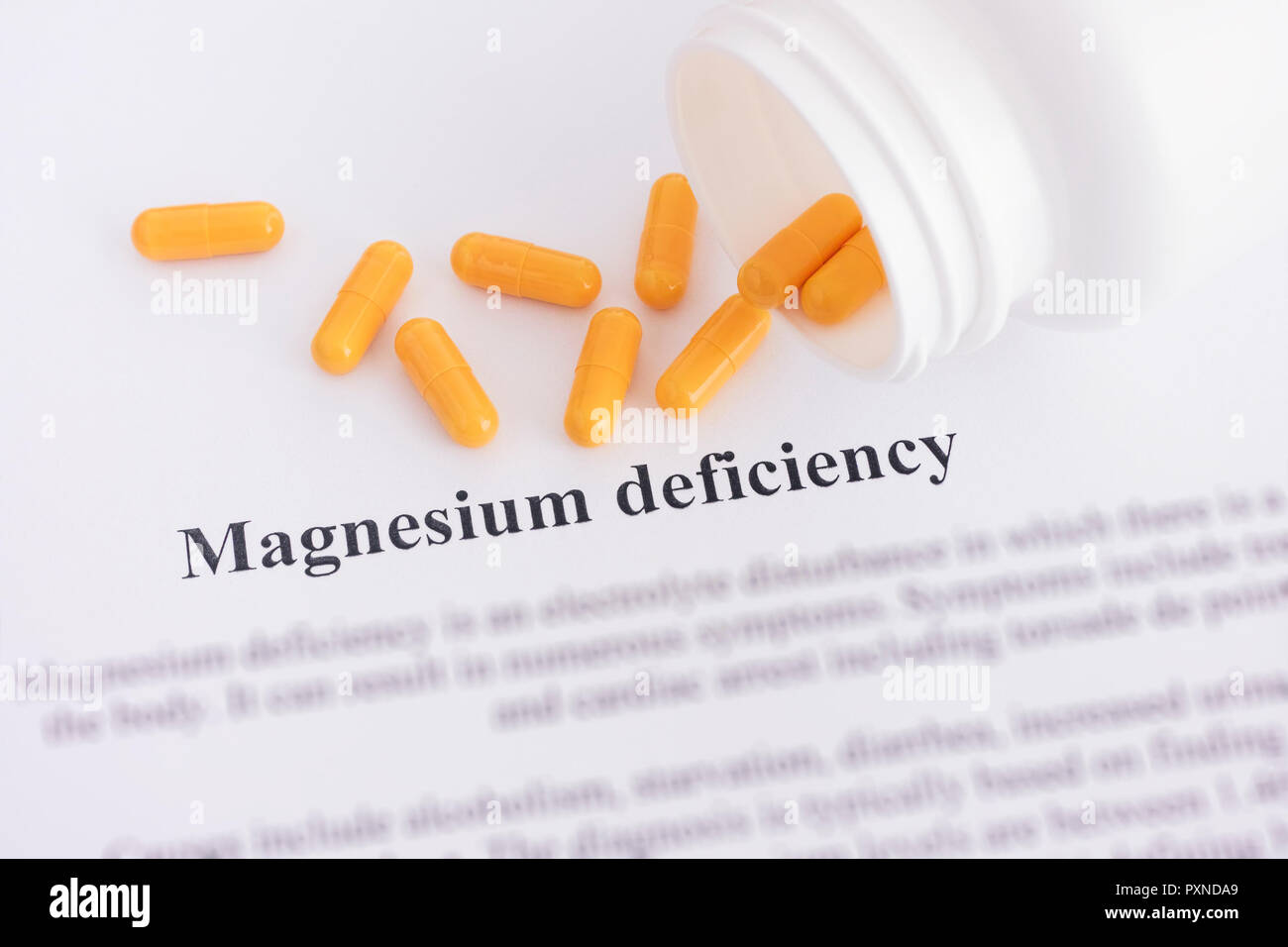 Magnesium deficiency diagnosis on paper with pills spilling out of a bottle. Close up. - Stock Image