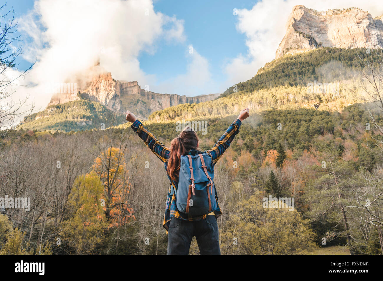 Spain, Ordesa y Monte Perdido National Park, back view of happy woman with backpack looking at view - Stock Image