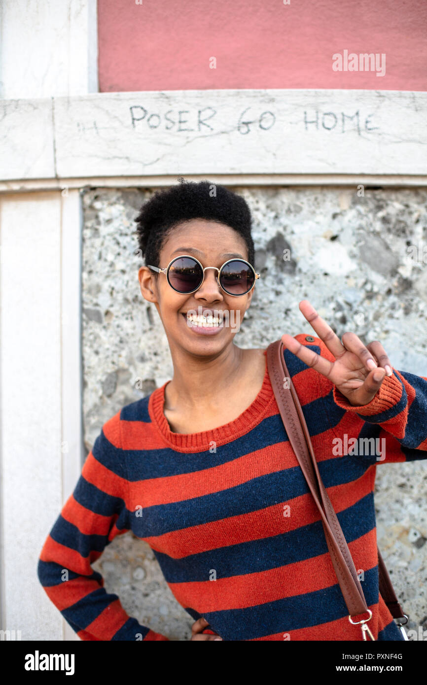 94be63ca54f Portrait of smiling young woman wearing sunglasses and striped pullover  showing victory sign - Stock Image