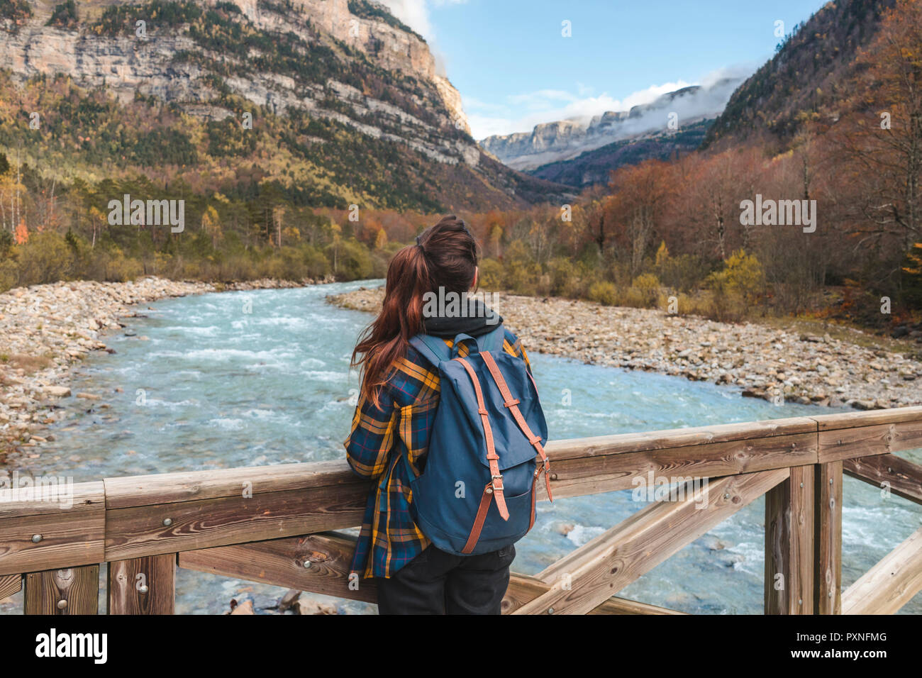 Spain, Ordesa y Monte Perdido National Park, back view of woman with backpack on wood bridge - Stock Image