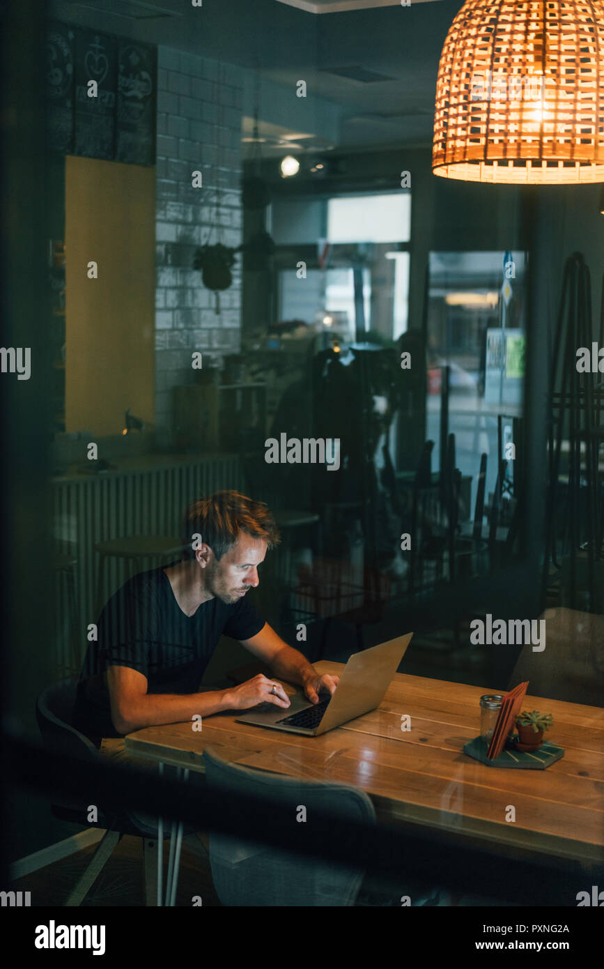 Man working overtime in his own start up business - Stock Image